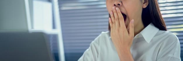 Azjatycka kobieta ziewa zakrywający otwartego usta i pokazywać śpiącego gest. uczucie zmęczenia po ciężkiej pracy w nocy.