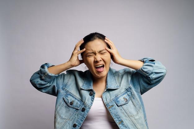 Azjatycka kobieta zły i krzyczy na białym tle.