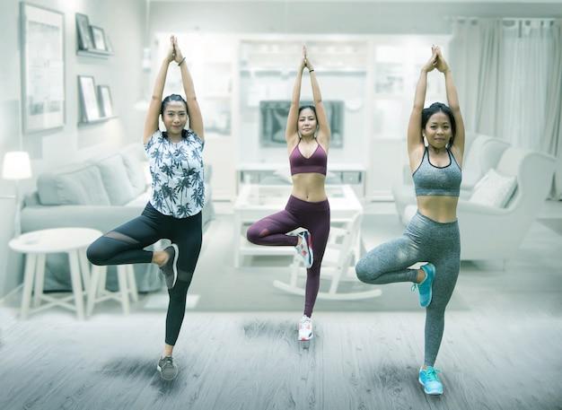 Azjatycka kobiety grupy praktyki joga w domu