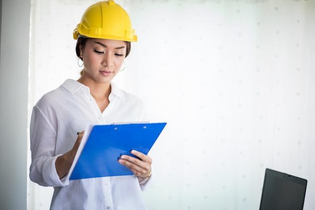 Azjatycka kobiety inżynieria sprawdza, pracuje i trzyma projekty przy biurem