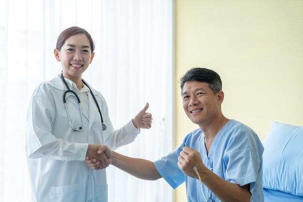 Azjatycka kobiety lekarka daje uścisk dłoni hre pacjentowi w szpitalu lub klinice