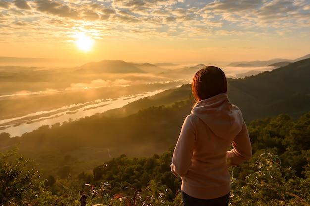 Azjatycka kobiety pozycja, oglądający wschód słońca i morze mgła przy mekong rzeką, tajlandia