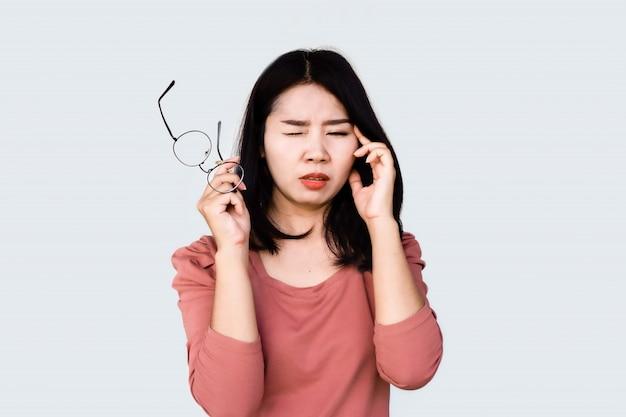 Azjatycka kobiety ręki mienia eyeglasses i nacieranie jej oko ból