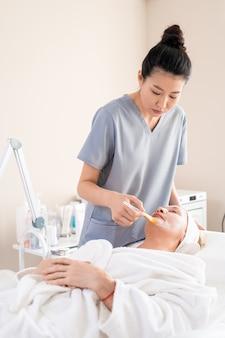 Azjatycka kosmetyczka w peelingach nakłada maseczkę na twarz dojrzałych klientów za pomocą pędzla w gabinecie kosmetycznym