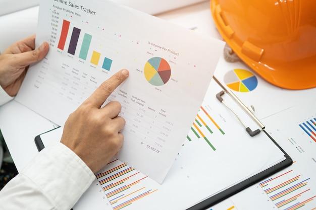 Azjatycka księgowa pracująca i analizująca projekty raportów finansowych.