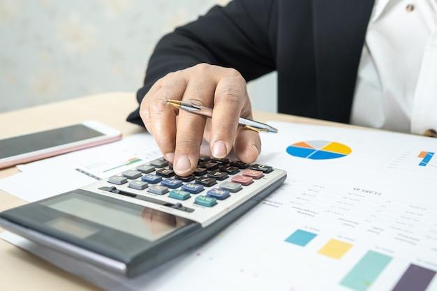 Azjatycka księgowa pracuje i analizuje raporty finansowe, księgowość projektów z wykresem wykresu i kalkulatorem