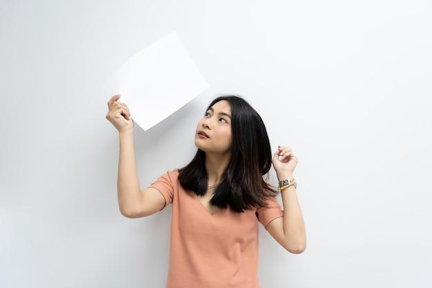 Azjatycka ładna kobieta pokazuje pusty biały papier