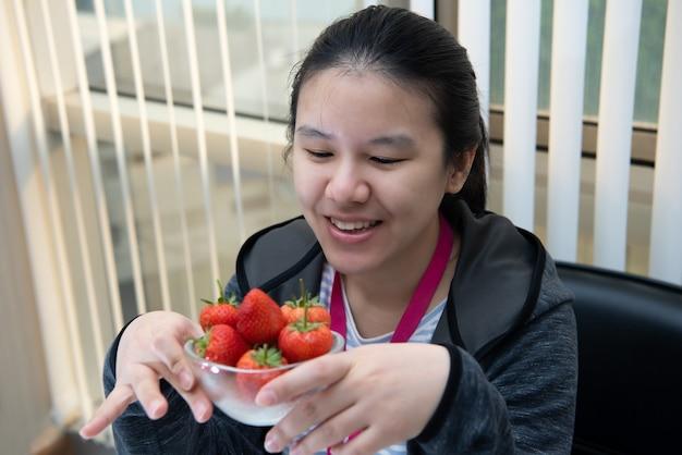 Azjatycka ładna kobieta trzyma i je świeże truskawki