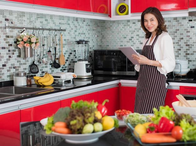 Azjatycka ładna kobieta w średnim wieku w fartuchu przy użyciu komputera typu tablet łączy się z internetem w kuchni z uśmiechniętą twarzą i radosnym sposobem. koncepcja nowoczesnego stylu życia gospodyni domowej.