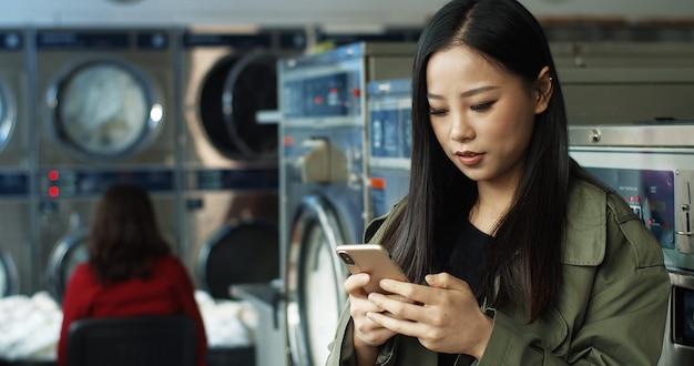 Azjatycka ładna kobieta z stukaniem i texting wiadomością na smartphone z długim ciemnego włosy podczas gdy stojący w pralnianym usługowym pokoju. piękna kobieta, wpisując na telefon i czekając na pranie.
