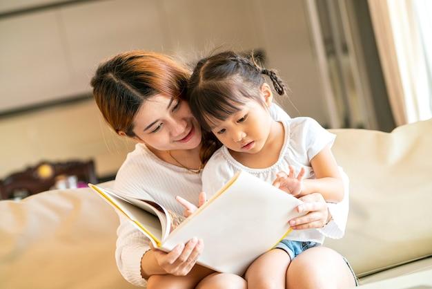Azjatycka ładna mama i jej szczęśliwa córka czytają książkę razem na wygodnej kanapie w salonie