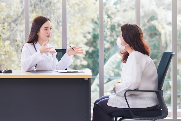 Azjatycka lekarka, która nosi fartuch medyczny, rozmawia z pacjentką, aby zasugerować wytyczne dotyczące leczenia