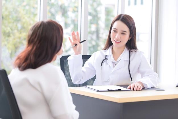 Azjatycka lekarka, która nosi płaszcz medyczny, rozmawia z kobietą w podeszłym wieku, aby zasugerować leczenie