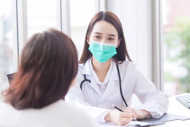 Azjatycka lekarka rozmawia ze swoim pacjentem, gdy nosi medyczną maskę na twarz w szpitalu w zdrowiu