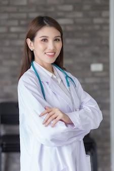 Azjatycka lekarka stojąca z rękami skrzyżowanymi szczęśliwa i uśmiechnięta w szpitalu