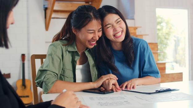 Azjatycka lesbijska lgbtq kobiet para podpisuje kontrakt w domu