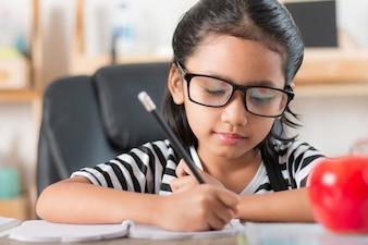 Azjatycka mała dziewczynka robi pracie domowej