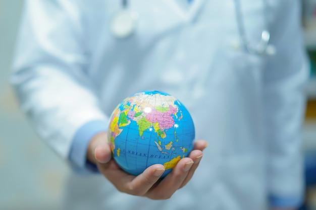 Azjatycka mądrze mężczyzna lekarka trzyma światową kulę ziemską.