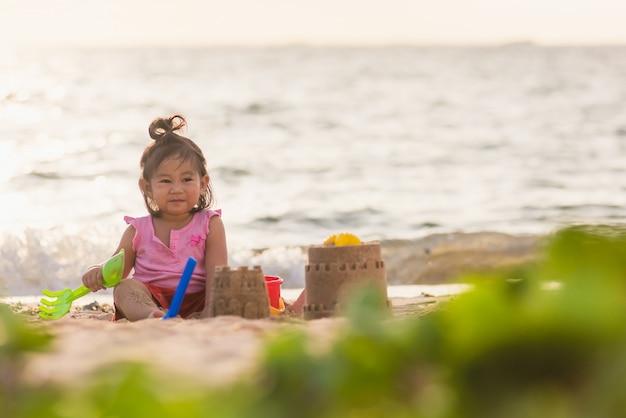 Azjatycka mała dziewczynka bawi się piaskiem z zabawkowymi narzędziami do piasku na tropikalnej plaży morskiej