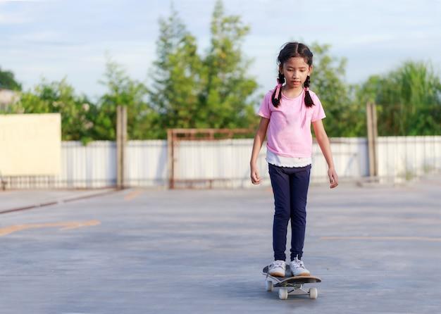 Azjatycka mała dziewczynka bawić się deskorolka i ono uśmiecha się z szczęścia againts niebieskim niebem