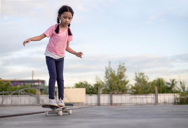 Azjatycka mała dziewczynka bawić się deskorolka