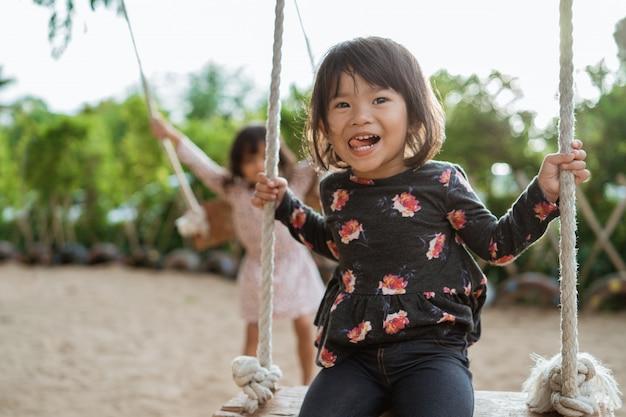 Azjatycka mała dziewczynka cieszy się bawić się huśtawkę przy boiskiem