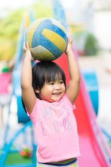 Azjatycka mała dziewczynka cieszy się bawić się piłkę w dziecka boisku