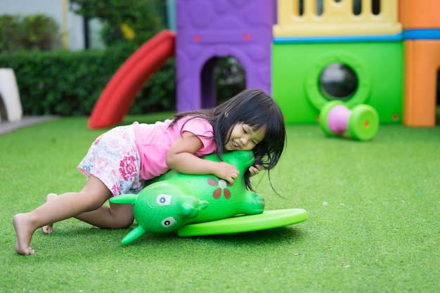 Azjatycka mała dziewczynka cieszy się bawić się w dziecka boisku