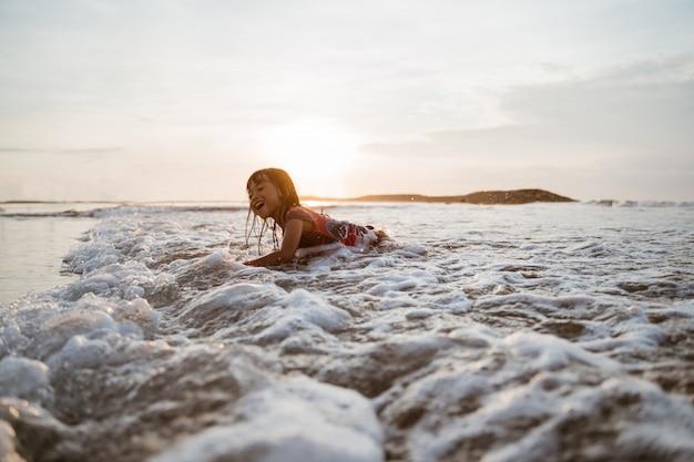 Azjatycka mała dziewczynka czołgać się na piasku w plaży podczas gdy bawić się z wodą