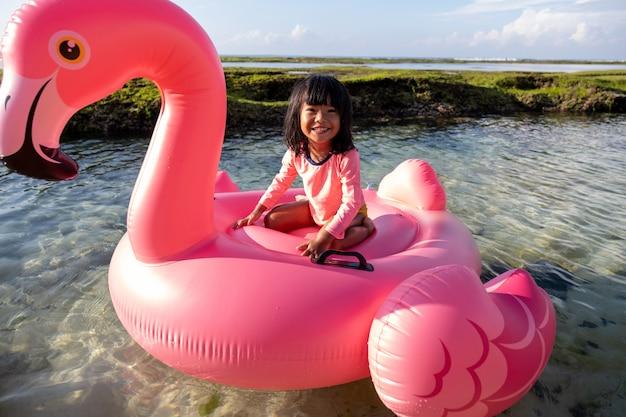 Azjatycka mała dziewczynka jedzie flaminga unosi się na plaży