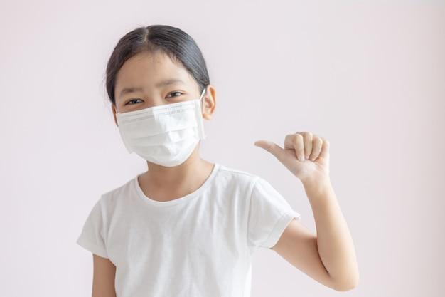 Azjatycka mała dziewczynka jest ubranym ochronną medyczną maskę