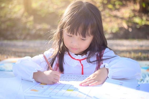 Azjatycka mała dziewczynka leży, rysuje lub odrabia lekcje w papierowej książce dla dzieci w wieku przedszkolnym w parku przydomowego ogrodu.