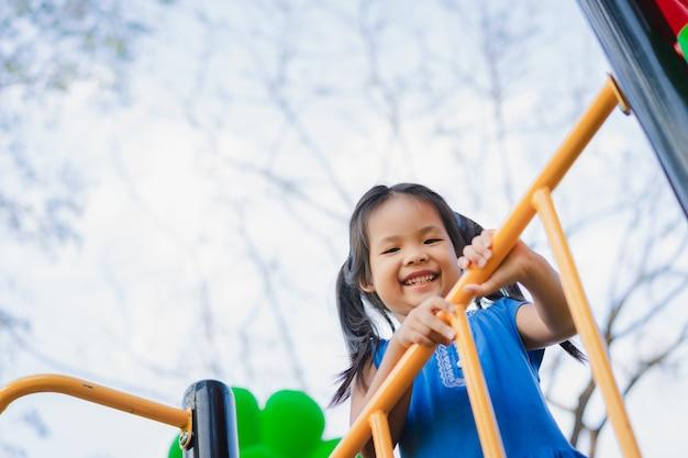 Azjatycka mała dziewczynka lubi bawić się na placu zabaw dla dzieci