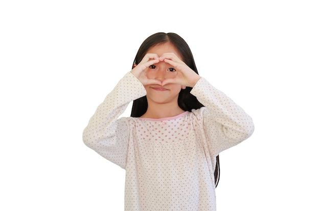 Azjatycka mała dziewczynka robi palce na znak serca na oczach na białym tle