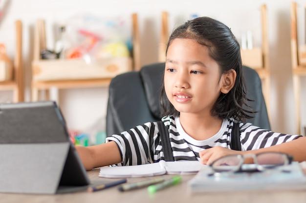 Azjatycka mała dziewczynka robi pracie domowej na drewnianej stół wybiórki ostrości płytkiej głębii pole