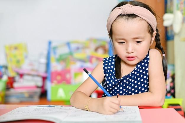 Azjatycka mała dziewczynka robi szkolnej pracie domowej od domu