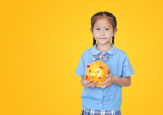 Azjatycka mała dziewczynka w mundurka szkolnego mienia prosiątka banku odizolowywającym z kopii przestrzenią. uczennica z koncepcja oszczędzania pieniędzy.