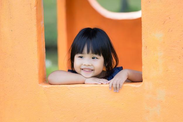 Azjatycka mała dziewczynka w okno cieszy się bawić się w dziecka boisku