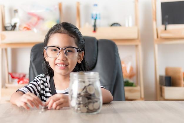 Azjatycka mała dziewczynka w ono uśmiecha się z monetą