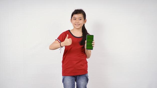 Azjatycka mała dziewczynka w porządku ekran smartfona na białym tle