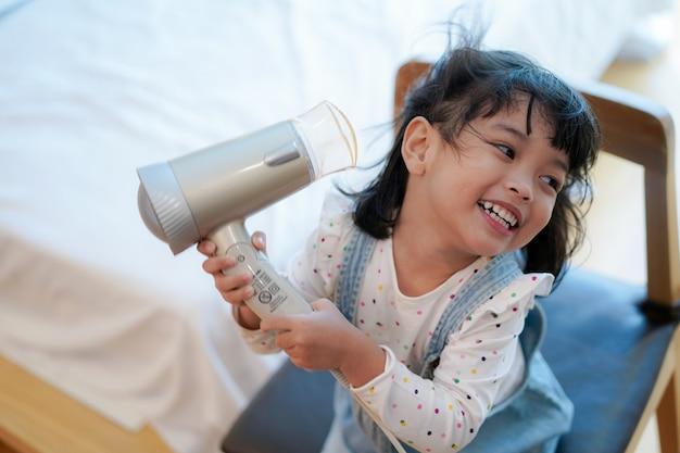 Azjatycka mała dziewczynka z lokówkami lub suszarką do włosów na głowie i suszy włosy po kąpieli.