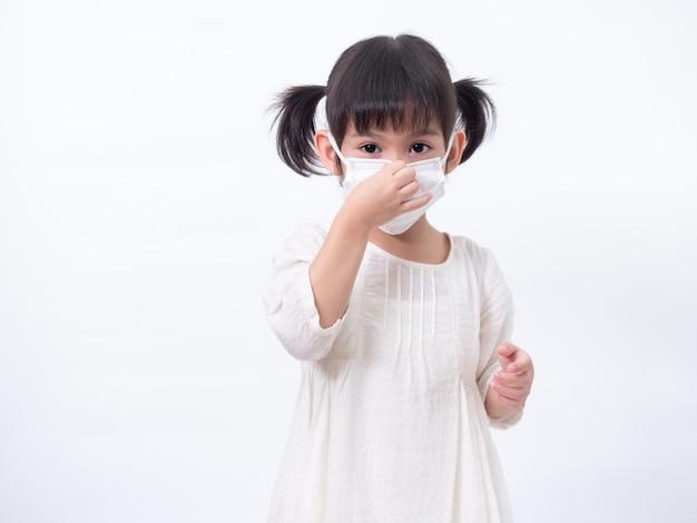 Azjatycka mała śliczna dziewczyna 4 lata ubrana w higieniczną maskę do ochrony przed rozprzestrzenianiem się wirusa korony covid-19 przeziębieniem lub zanieczyszczeniem na białej ścianie