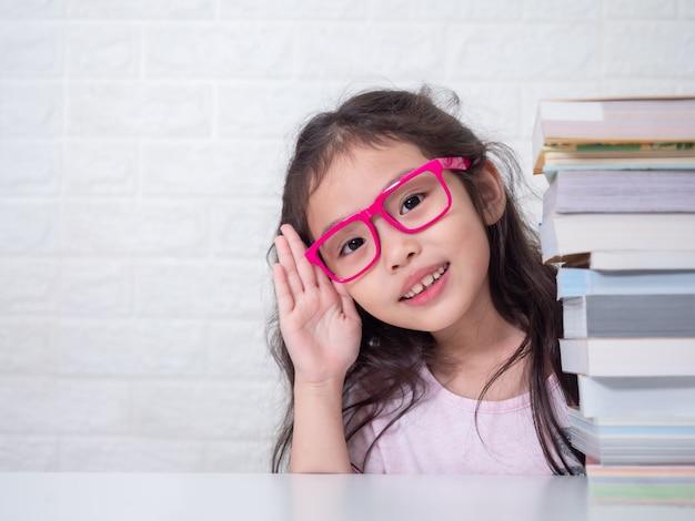 Azjatycka mała śliczna dziewczyna jest ubranym różowych szkła i chuje z stosem książki. dziecko w wieku przedszkolnym z książką.