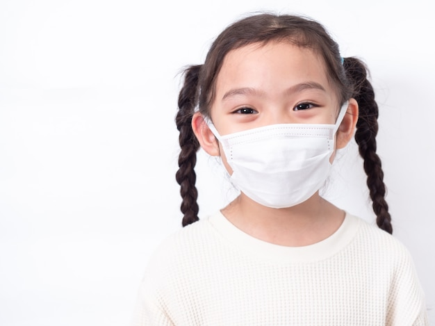 Azjatycka mała śliczna dziewczyna w wieku 6 lat ubrana w higieniczną maskę na twarz do rozprzestrzeniania wirusa korony covid-19 przeziębienia lub zanieczyszczenia na białej ścianie