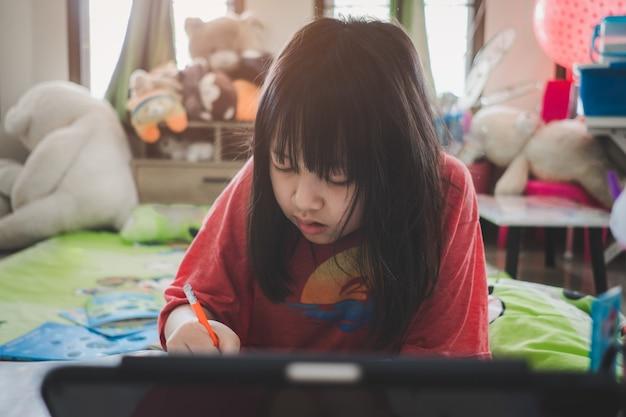 Azjatycka mała uczennica studiująca podczas lekcji online w domu z uśmiechem i szczęśliwym dystansem społecznym podczas kwarantanny, koncepcja edukacji online
