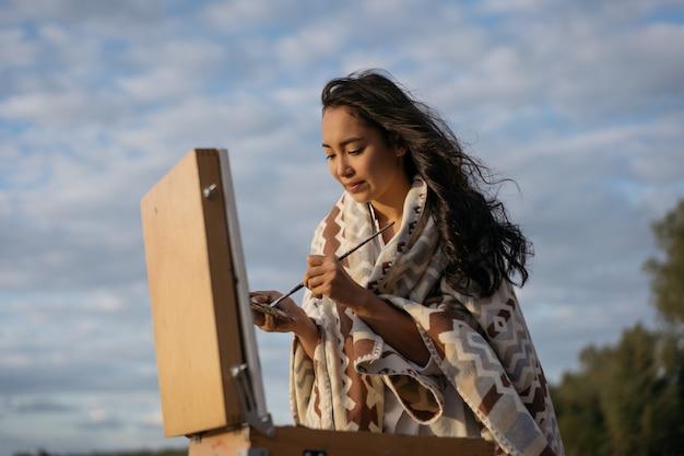 Azjatycka malarz poszukująca inspiracji, ciesząca się pięknymi krajobrazami, trzymająca pędzel i paletę