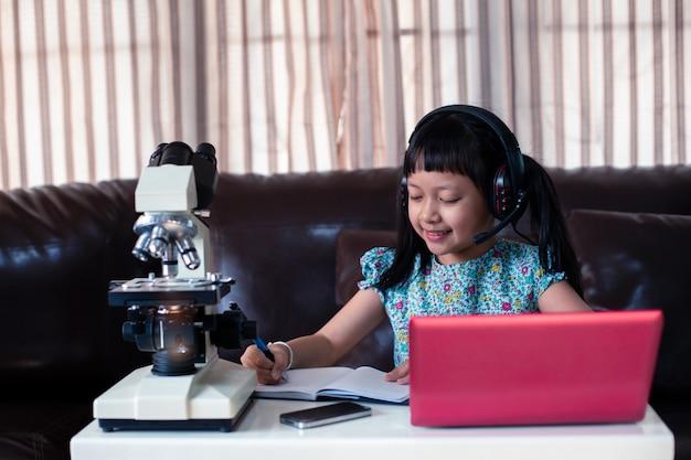 Azjatycka małe dziecko dziewczyna jest ubranym hełmofony uczy się online używać laptop i mikroskop w domu, dystansowa edukacja
