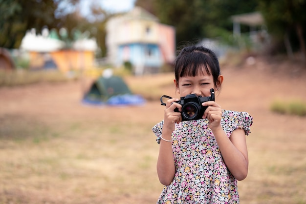 Azjatycka małe dziecko dziewczyny mienia filmu kamera i brać fotografię