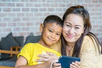 Azjatycka mama i chłopiec bawić się mądrze telefon