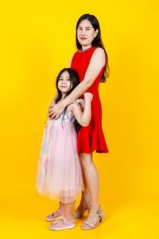 Azjatycka mama i córka biorąc zdjęcie portretowe razem na żółtym tle z zabawnym i pięknym.